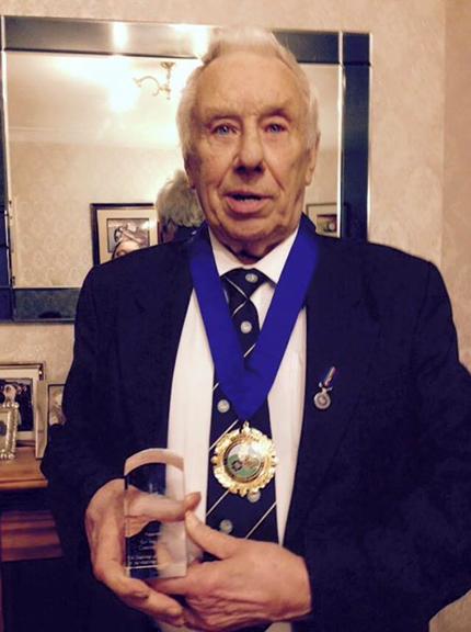Jeffrey Casciani-Wood proudly holding his lifetime achievement award