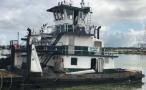 NTSB determines that the probable cause of the capsizing and sinking of the Gracie Claire was the towing vessel's decreased stability and freeboard due to undetected flooding through a hull leak in the rudder compartment, which made the vessel susceptible to the adverse effects of boarding water from the wake of a passing vessel.