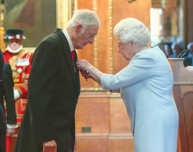Norman Finlay MBE receiving his award from Her Majesty The Queen in 2018