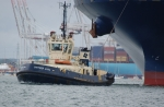 Tug at work towing a large container ship