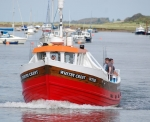 Fishing vessel sets out from Wells-Next-The-Sea at high tide